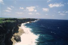 約2キロ続く断崖の先に残波岬灯台が見える
